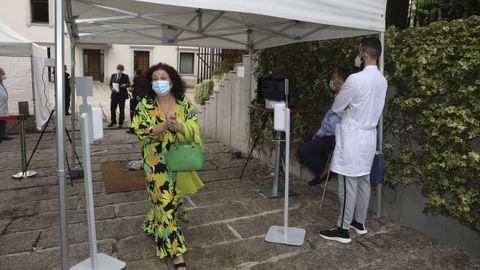Una invitada al acto pasa por el control sanitario instalado a la entrada del Parlamento