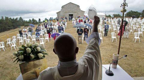 El cura Xabier Diéguez levanta una mascarilla ante los fieles que acudieron el 15 de agoto a la fiesta del monte Faro