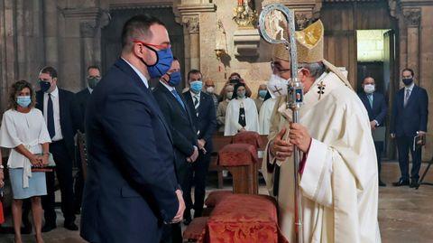 El arzobispo de Oviedo, Jesús Sanz Montes (dcha), saluda al presidente del Principado, Adrián Barbón, durante la eucaristía celebrada en la basílica de Covadonga a la que también han asistido el presidente del parlamento regional, Marcelino Marcos Líndez, y la delegada del Gobierno, Delia Losa, entre otros.