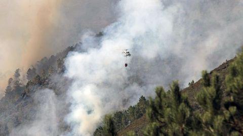 Un helicóptero entre el humo del frente del incendio más cercano a la carretera Quiroga-Folgoso