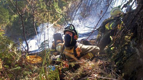 Integrantes de la brigada contraincendios de Quiroga se preparan para la descarga de un hidroavión que pasa sobre ellos