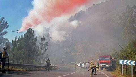 Un avión descarga agua con retardante coloreado de rojo junto a la carretera de Quiroga a Folgoso