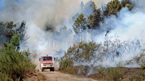 Un camión cargado de agua, entre el humo del incendio en una pista del monte comunal de A Ermida