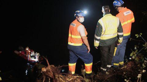 Dos sanitarios y un guardia civil observan desde la orilla cómo los bomberos rescatan desde una lancha el rescate del cuerpo del camionero