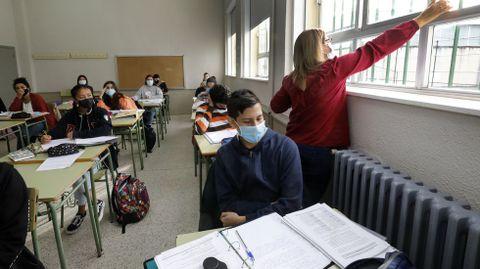 Una profesora abre las ventanas para ventilar un aula de secundaria