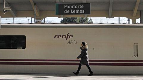 Una pasajera pasa frente a un tren Alvia detenido en la estación de Monforte