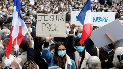 Una joven muestra la pancarta de recuerdo del profesor degollado este domingo en la plaza de la República de París