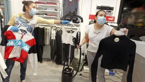 Imagen de archivo en la que dos trabajadoras desinfectan prendas en una tienda de Vilagarcía