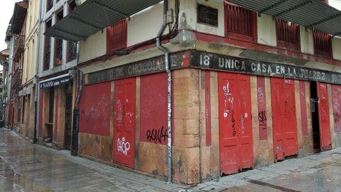 Entre las calles Canóniga y Mon de Oviedo aún queda el cartel de la que fue fábrica de chocolate La Popular, de Armando G. Ojanguren, que luego fundaría la famosa academia mercantil