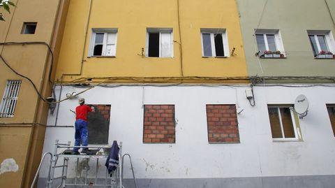 Un operario municipal tapia las ventanas de un local en el barrio de Recimil (Ferrol) para evitar que entren okupas
