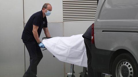 Miembros de los servicios funerarios recogen un cádaver del Hospital de Mataro