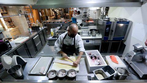 La cocina de Culuca (A Coruña), el sábado por la mañana. Chisco Jiménez, propietario del local, corta pescado mientras dos trabajadores preparan envases y ultiman los detalles de las placas de callos
