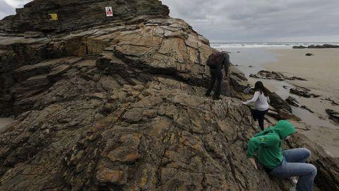 Pese a los avisos, la gente trepa a las rocas de As Catedrais, algo prohibido