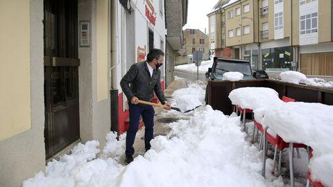 El propietario de un bar de O Cádavo limpiando de nieve la entrada de su negocio, sin suministro eléctrico este domingo