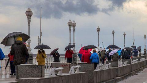 Varias personas caminan junto a la playa de San Lorenzo, en Gijón, durante el temporal
