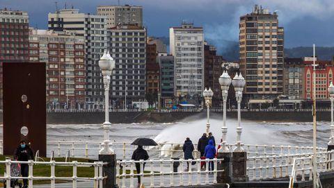 temporal olas.Varias personas caminan junto a la playa de San Lorenzo, en Gijón
