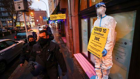 Policías alemanes pasan por delante de un bar reconvertido en tienda de artículos de protección contra el covid en Frankfurt