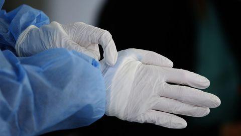 Chuac. Un sanitario colocándose los guantes para realizar las pruebas covid