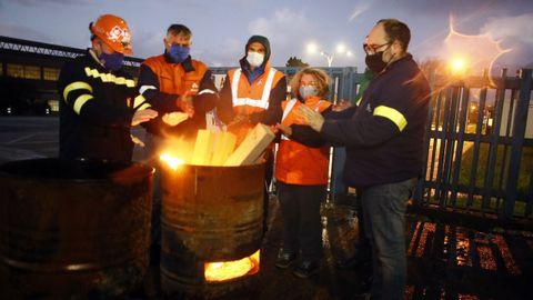 Trabajadores de Alcoa se calientan mientras hacen guardia en el exterior de la fábrica, que está en huelga desde hace dos meses