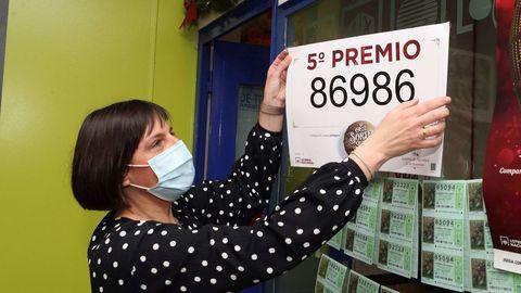 La propietaria de la administración de lotería 81 de Zaragoza coloca el cartel tras haber vendido décimos del número 86986 uno de los quintos premios