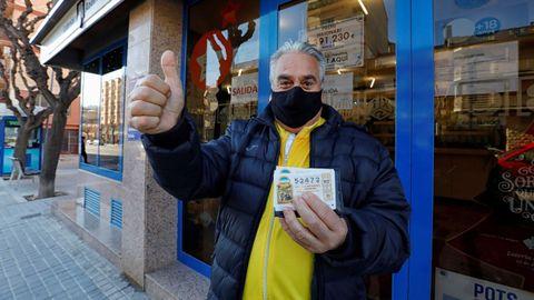 Juan, un vecino de Santa Margarida de Montbui (Barcelona) muestra el décimo premiado con el tercer premio de la Lotería de Navidad ante la administracion del pueblo que ha vendido una serie del 54.472