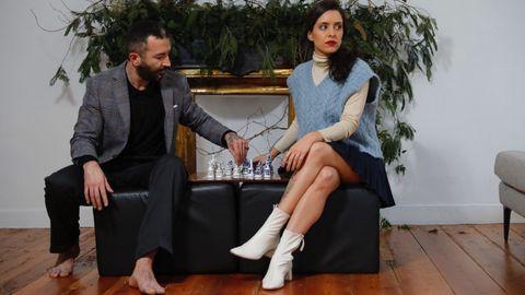 Néstor desafía a Marta el ajedrez con una chaqueta de Etiem. Marta lleva un chaleco de punto y un top brillante de Zara.
