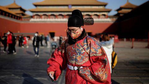 Un hombre vestido con ropas tradicionales chinas, en la Ciudad Prohibida de Pekín