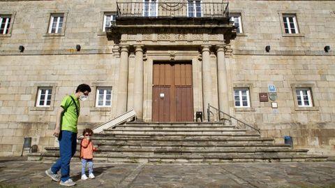 Un hombre pasea el pasado mes de mayo con su hijo junto a la puerta del Parador de Monforte, cerrado en aquel momento por la crisis del coronavirus