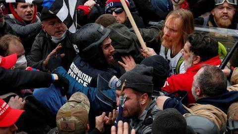 Seguidores de Trump rodean a un policía durante el asalto al Capitolio