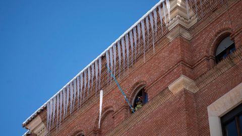 Un bombero retira carámbanos de hielo de la fachada de un edificio en Teruel