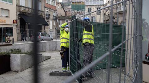 Dos obreros colocan una malla sobre las vallas instaladas a primera hora en la plaza Doutor Goyanes