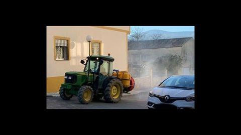 Un tractor contratado por el Ayuntamiento fumiga estos días con desinfectante una calle de Quiroga