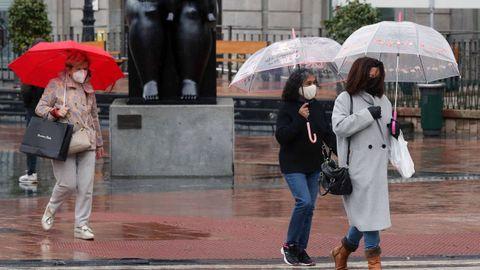 Varias mujeres se protegen de la lluvia con paraguas mientras pasean por una céntrica calle de Oviedo