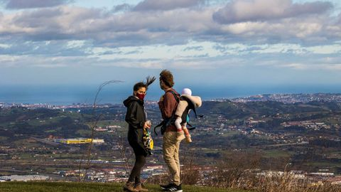 Una pareja intenta protegerse del viento en Gijón