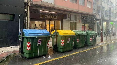 Contenedores de basura situados delante de un comercio de Pontevedra