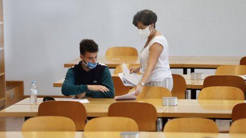 La distancia de seguridad que redujo los aforos de las aulas hizo que la pasada selectividad la relación entre estudiantes y docentes durante las pruebas fuese muy fluida. En la imagen, un alumno de UVigo recibe el examen de una profesora en la ABAU del pasado septiembre