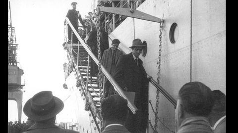Retornados españoles exiliados en la URSS descienden al puerto de Castellón desde el barco ruso Crimea. En la parte superior de la escalera, un oficial soviético supervisa el desembarco