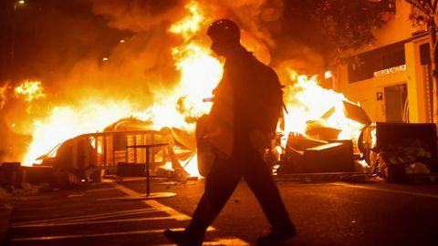 Un manifestante pasa delante de una barricada en llamas, durante las protestas en Barcelona contra el encarcelamiento de Pablo Hasel