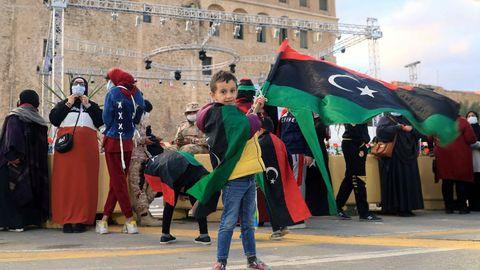 Un niño enarbola una bandera libia en la conmemoración en Trípoli del 10 aniversario del levantamiento popular contra Gadafi