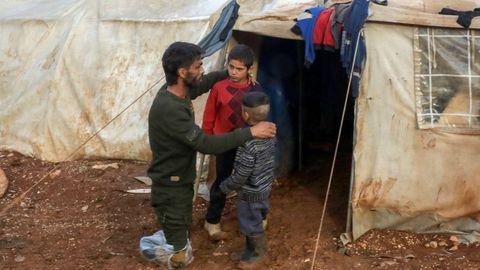 Ahmad Hamra y sus hijos fuera ante su tienda de campaña en un campamento sirio para desplazados, en el norte de Alepo