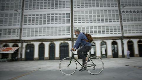 Un hombre pasea en bicicleta por la Marina, en A Coruña