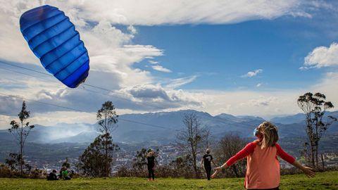 Un grupo de personas vuelan una cometa aprovechando el fuerte viento en la cumbre del monte Naranco