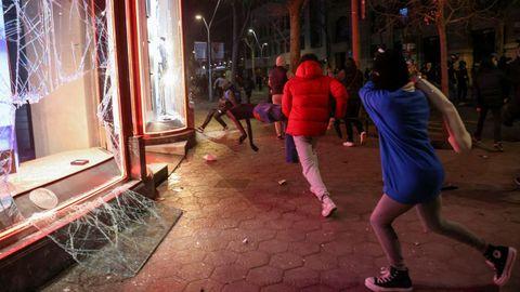 Un encapuchado destroza los cristales del escaparate de una tienda de ropa en Barcelona, el sábado por la noche, mientras otros saqueadores roban los maniquíes y las prendas