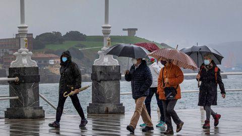 Varias personas pasean por el paseo de la Playa de San Lorenzo de Gijón