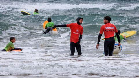 Dos monitos con un grupo de surfistas en la playa de San Lorenzo en Gijón