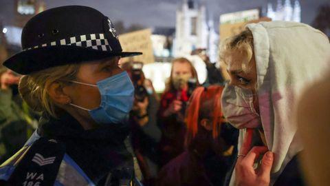 Una manifestante se enfrenta a un policia durante la vigilia de la noche del sábado
