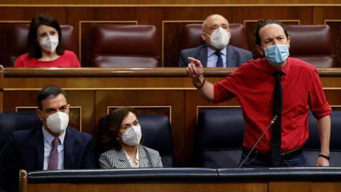 El vicepresidente segundo del Gobierno, Pablo Iglesias, interviene en la sesión de control bajo la mirada del presidente del Ejecutivo, Pedro Sánchez, y la vicepresidenta primera, Carmen Calvo.