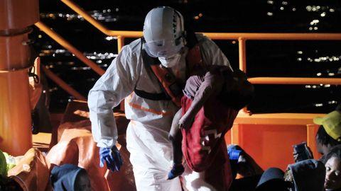 Un tripulante de la Salvamar Macondo traslada a la pequeña al muelle