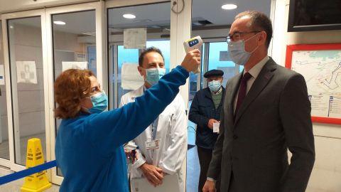 Una sanitaria toma la temperatura al consejero de Salud, Pablo Fernández Muñiz, en presencia del gerente de área sanitaria V, Manuel Bayona, en el hospital de Cabueñes
