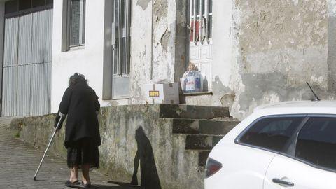 María José caminando por delante de su casa, con la compra en la puerta